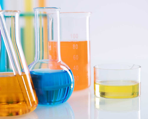 Closeup shot of different flasks with colorful liquids on a white background in a lab